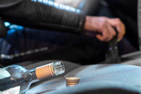 Drunk driving concept. Young man driving car under the influence of alcohol. Hand on gear stick. Close up of empty bottle of wine on front seat. Traffic safety risk.