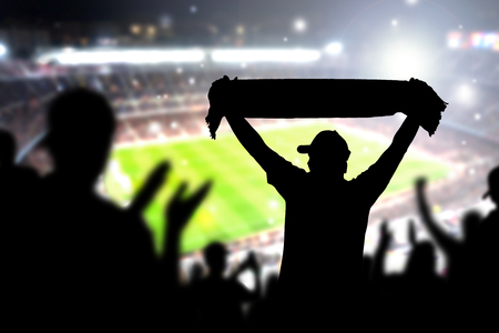 Crowd and fans in football stadium. People in soccer game. Person celebrating goal and holding merchandise scarf for favourite club and team in match. Happy live sport silhouette audience cheering.