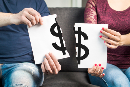 Fight about money or financial argument concept. Man and woman holding ripped paper with dollar sign. 스톡 콘텐츠