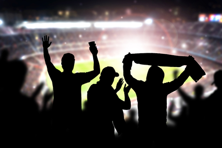 Friends at football game in soccer stadium. Crowd cheering and celebrating a goal in arena during match. Silhouette people in live sport audience having fun. Archivio Fotografico