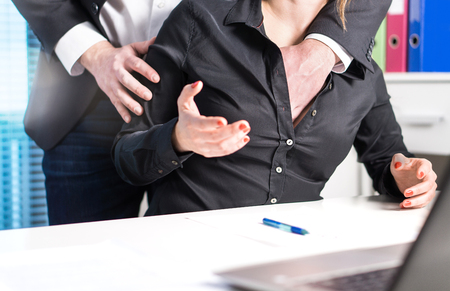Sexual harassment and abuse at work concept. Man groping woman in business office. Boss putting hand inside her shirt and touching breasts without permission. Archivio Fotografico