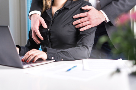 Sexual harassment and abuse at work concept. Man groping woman in business office. Boss touching breasts.