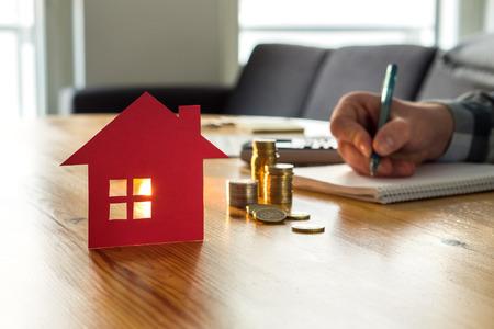 Hombre contando el precio de la casa, el costo del seguro del hogar, el valor de la propiedad o el alquiler en papel. Oferta por escrito de agente inmobiliario o agente inmobiliario. Hipoteca, ahorro y compra de piso. Dinero y pequeño edificio en mesa. Foto de archivo