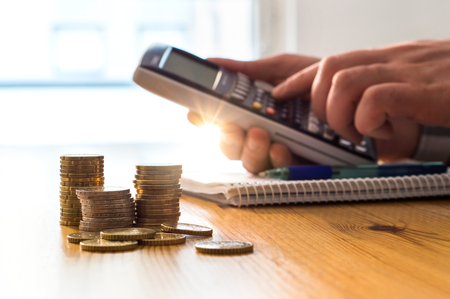 Man using calculator to count money savings and living costs. Inflation, taxes and rising expenses. Calculating daily family groceries price and budget. Stack of coins on table.