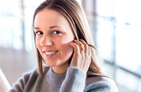 Beautiful young woman smiling and touching hair with hand in modern office or business building. Happy person looking at the camera. Wearing casual sweater at work. Portrait of successful woman.