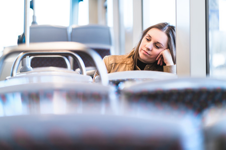 Sad tired woman in train or bus. Bored or unhappy passenger sitting in tram leaning against hand. Upset lady on a late delayed bus. Negative public transportation concept. Stockfoto