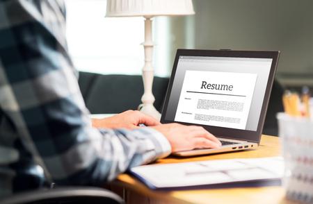 Hombre escribiendo curriculum vitae y CV en la oficina en casa con ordenador portátil. Solicitante que busca un nuevo trabajo y mecanografía el curriculum vitae para su aplicación. Búsqueda de empleo, caza y desempleo. Simulacros de texto en la pantalla de la computadora.