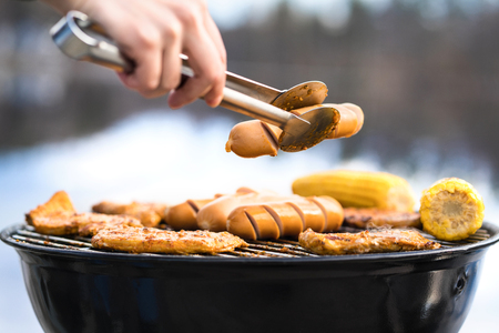 Person grilling with charcoal kettle grill full of delicious food. Cooking in outdoor kitchen in nature. Man or woman holding sausage with barbeque tongs in hand. Summer camping and bbq at beach.