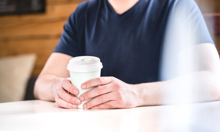 Man holding take away coffee cup in hands on table in cafe, coffee shop or home. Guy with hot chocolate or tea.