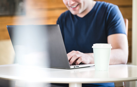 Happy man using laptop with take away coffee cup on table. Smiling person with computer home or in cafe. Banco de Imagens