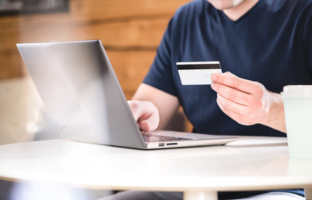 Man holding credit card and typing bank information or identification numbers with laptop. Ecommerce and online shopping concept.