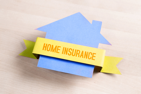 Home insurance concept. Property protection, safety, security and finance. Cardboard paper house and building on table.