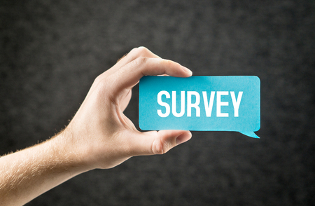 Survey. Giving feedback, market research, questionnaire, user experience and review concept. Hand holding cardboard paper speech bubble on dark background.