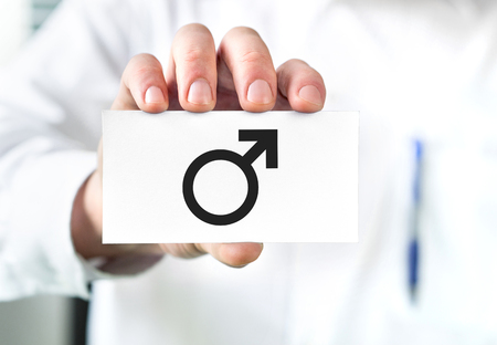 Male health concept. Doctor holding business card with man symbol. Urologist or specialist.
