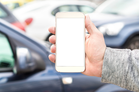 Man holding smartphone with empty blank white screen. Many cars or traffic in background. Mobile phone in hand. Template for navigation, parking or ride share app. Transportation smart application.