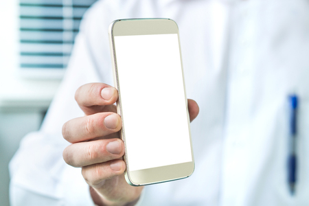 Doctor holding smartphone with empty blank white screen. Medical professional, physician, nurse or dentist showing mobile phone with copy space. Banco de Imagens