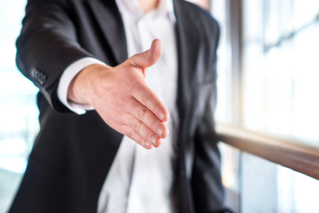 Success, opportunity, deal or agreement. Business man offering and giving hand for handshake in modern office building.