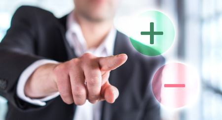 Pros and cons concept. Business man touching plus or minus symbol. Choosing between two options.