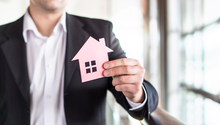 Architect, banker, realtor, agent, businessman or broker holding paper house. Real estate or architecture business. Rental apartment, mortgage, bank loan, buying home or insurance concept.