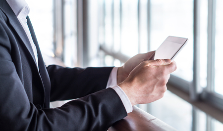 Business man using tablet or reading news with tablet. Businessman working in modern office building with smart mobile device.