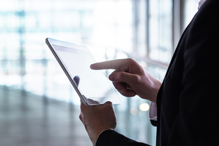 Man in a suit using tablet. Businessman with smart mobile device in modern glass building. Banco de Imagens