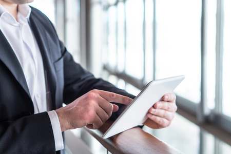 Business man using tablet by the window in modern glass office building. Businessman holding smart mobile device and working. Pressing touch screen with one finger.