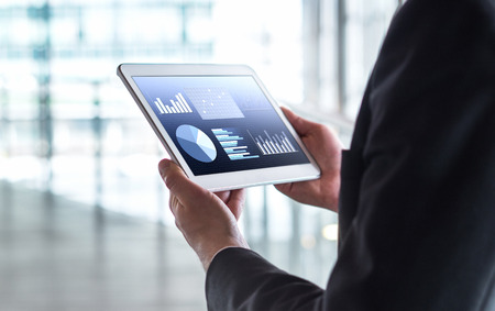 Man reading financial statistics, business graphs and trade data. Businessman using tablet in modern office building. Banco de Imagens