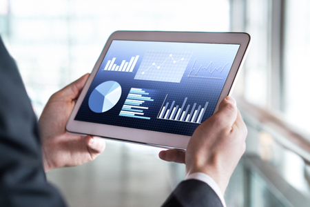 Close up of businessman using tablet in modern office building. Man reading financial statistics, business graphs and trade data.