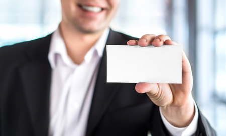 Happy smiling business man holding empty white business card in modern office building. Free blank copy space.