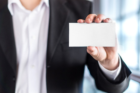 Professional business man holding empty white business card in modern office building. Free blank copy space. Banco de Imagens
