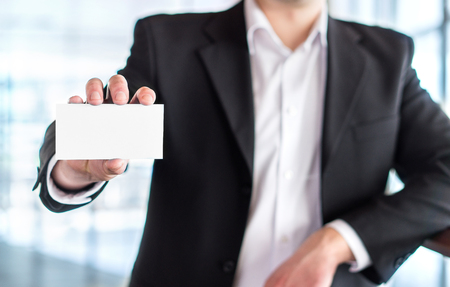 Casual business man holding empty white business card in modern office building. Free blank copy space.