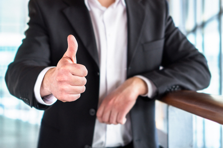 Business man or lawyer giving thumbs up in modern office building. Happy businessman showing satisfied and supportive hand gesture. Banco de Imagens