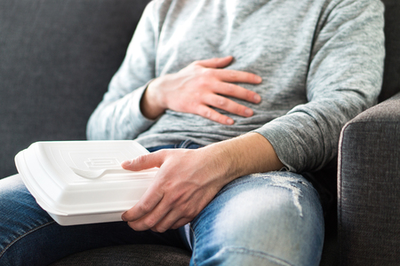 After eating fast food. Man feeling full or taking nap after eating junk. Guy having hangover or unhealthy diet. Stomach pain while sitting on couch. Stockfoto