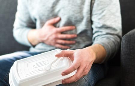 Mann mit Durchfall oder Lebensmittelvergiftung nach ungesundem Junk Fast Food. Guy muss auf die Toilette gehen, nachdem er zu viel gegessen hat. Magenschmerzen, Verdauungsprobleme, Verdauungsstörungen, Salmonellen oder Herzinfarkt.
