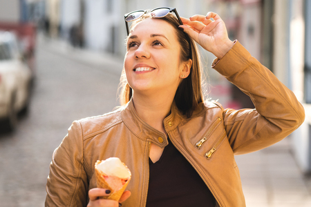 Happy woman eating ice cream and lifting sunglasses and looking up. Tourist in old town with sweet dessert during travel. Positive lifestyle at sunset in the city.