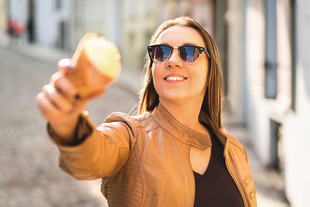 Smiling woman showing and pointing an ice cream cone at camera. Person goofing and messing around with sweet dessert in the city.