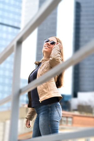 Happy young woman in big city with high buildings and skyscrapers. Stylish and confident lady with sunglasses. Vertical shot.