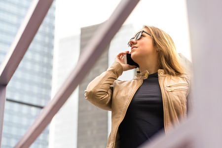 Woman talking on the phone in the city. Lady calling with smartphone. Neutral or serious face. Banco de Imagens