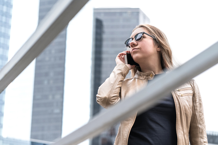 Frustrated woman talking on the phone in the city. Annoyed or serious lady with smartphone having stress.