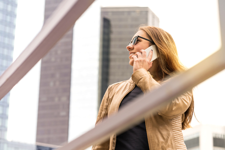 Happy woman talking on the phone in big city with high tall buildings and skyscrapers. Businesswoman having conversation with smartphone. Banco de Imagens