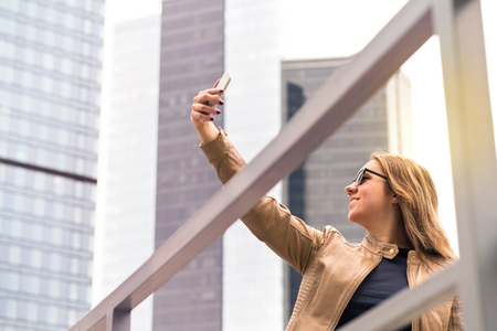 Young happy woman taking selfie in city street. Smiling lady taking photo of herself with smartphone camera. Mobile phone photography. Banco de Imagens