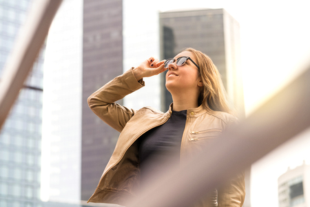 Successful young woman in big city with high buildings and skyscrapers. Stylish and confident lady with sunglasses. Banco de Imagens