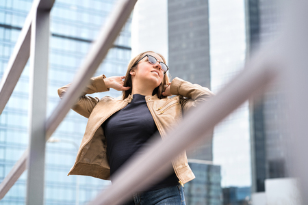 Independent, confident and powerful woman in city. Happy healthy model with sunglasses and good fashion style. Big, tall and high modern office buildings. Lady posing hands in hair. Banco de Imagens