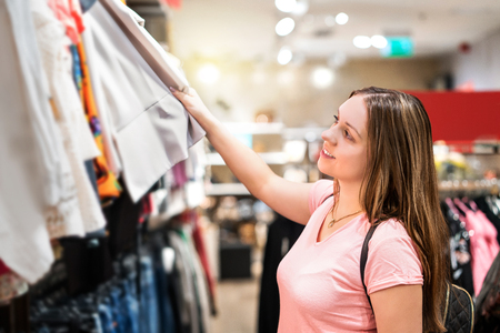 Young woman shopping in clothing store. Happy girl looking at clothes in shop at mall. Smiling student choosing outfit.
