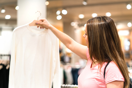 Woman holding blouse in hanger in fashion store. Shopping for sweater or shirt. Happy customer and shopper looking for new clothing. Banco de Imagens