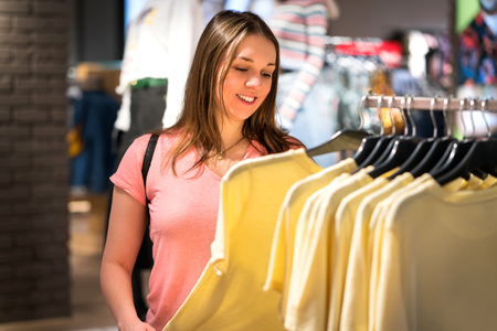 Woman shopping in fashion store during sale and clearance. Buying and choosing clothes from rack in shopping center. Happy customer looking at t-shirts.