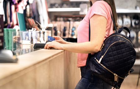 Woman at checkout in fashion store paying with credit card. Customer using payment terminal machine. Standing at counter. Buying and shopping for clothes. Bank card graphics are made up. Banco de Imagens
