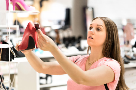 Shocked woman looking at price tag of too expensive shoes in fashion store while shopping. Unhappy customer holding high heels. Sad shopper with overpriced product.