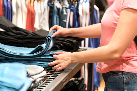 Buying and shopping for new pair of jeans. Woman picking the right size from stack.