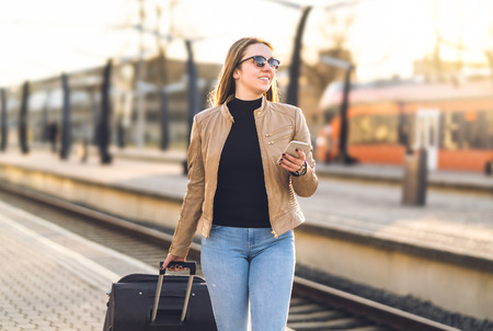 Woman walking in train station with smartphone. Happy female traveler pulling suitcase and baggage in platform while holding mobile phone. Banco de Imagens